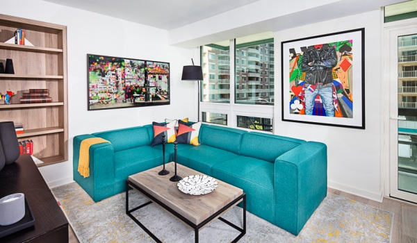 Living Area With Teal Sofa, Coffee Table, Modern Artwork And Windows With View Of Balcony At J Sol Apartments In Arlington, VA